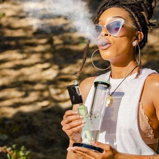 Photo of a woman using an Airis Dabble waterpipe attachment.